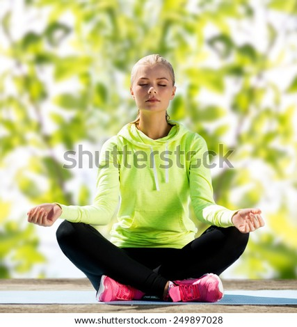 sport, fitness, yoga and people concept - happy young woman meditating in lotus pose and sitting on mat over green tree leaves background - stock photo
