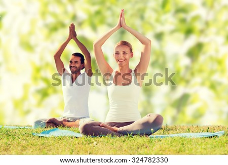 sport, fitness, yoga and people concept - smiling couple meditating and sitting on mats with raised hands over green tree leaves background - stock photo