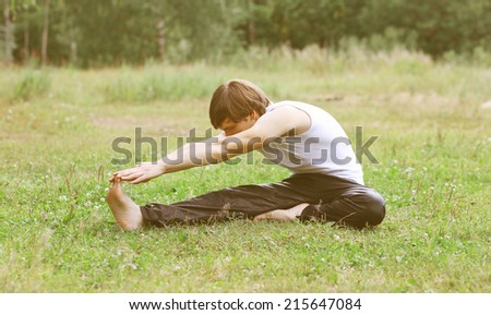Sport, fitness, yoga - concept, man doing exercise on the grass - stock photo