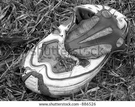 sport footwear, black and white trainers abandoned in the grass - stock photo