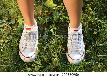 Sport Footwear on Female Feet on Green Grass