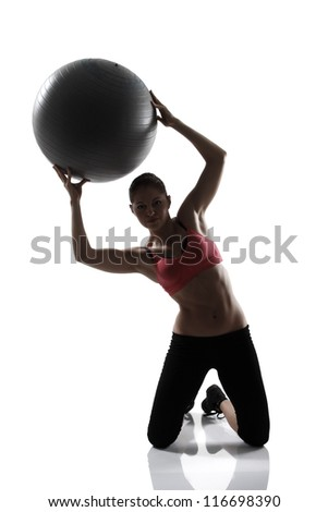 sport girl doing hands and abs exercise with fitness ball, silhouette studio shot over white background - stock photo