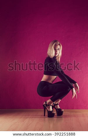 Sport girl in a slinky black dress with heels is dancing in the background of a pink wal