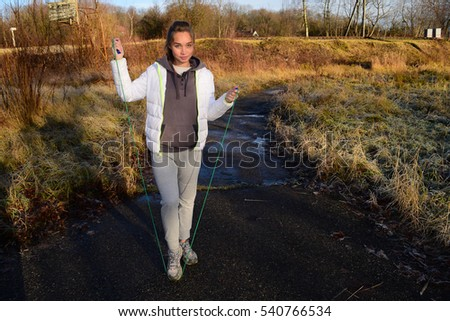 Sport girl jumping rope near the nature