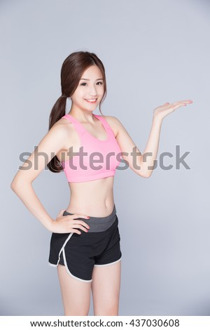 Sport girl showing something isolated on gray background. Running fitness sport woman smiling happy. asian beauty - stock photo