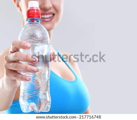 Sport. Girl with bottle of water - stock photo