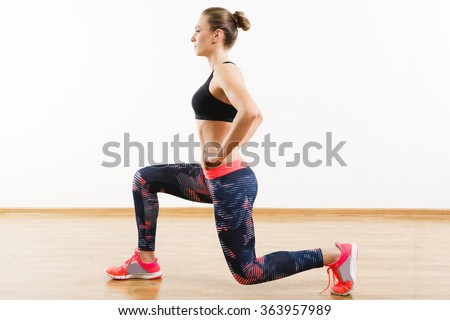 Sport girl with dark hair wearing pink snickers, dark leggings and black short top doing lunge at gym, fitness, white wall and wooden floor, copy space.