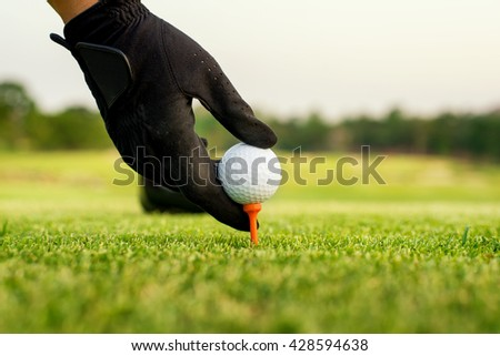 Sport, Golf concept - Hand hold golf ball with tee on course, close-up at golf ball and tee  - stock photo