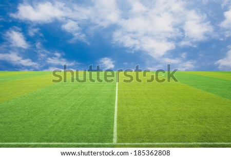 Sport grass field against the sky clouds - stock photo