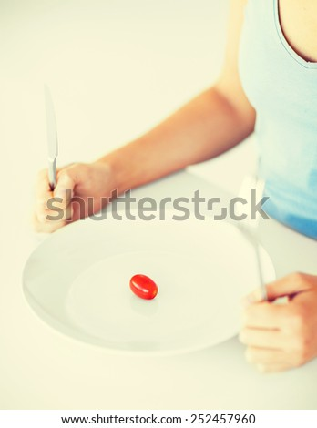 sport, healthcare and diet concept - woman with plate and one tomato - stock photo