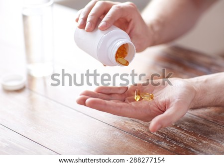 sport, healthy lifestyle, medicine, nutritional supplements and people concept - close up of man with glass of water pouring fish oil capsules from jar to hand - stock photo