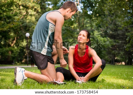 Sport injury - young fitness woman holding her ankle  with pain, man is helping - stock photo
