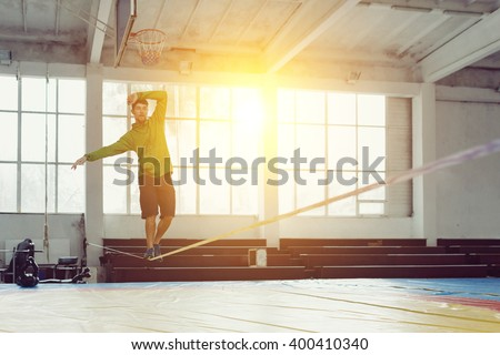 Sport, leisure, recreation and healthy active lifestyle concept - man slacklining walking and balancing on a rope, slackline in a sports hall - stock photo