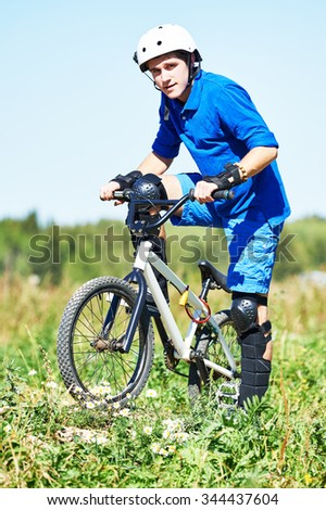 Sport lifestyle concept. Full-length portrait of young cyclist with his mountain bike bicycle outdoors on the meadow