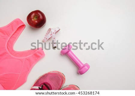 Sport lifestyle concept. Top view of dumbbell, apple, measuring tape, sneakers and sport accessories on white desk. - stock photo