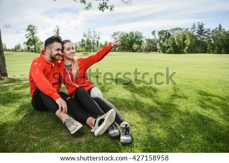 Sport man and woman making selfie in green park or forest while sitting on green grass. Happy couple hugging and posing for camera.