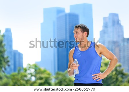 Sport man drinking water bottle in New York City. Male runner sweaty and thirsty after run in Central Park, NYC, Manhattan, with urban buildings skyline in the background. - stock photo