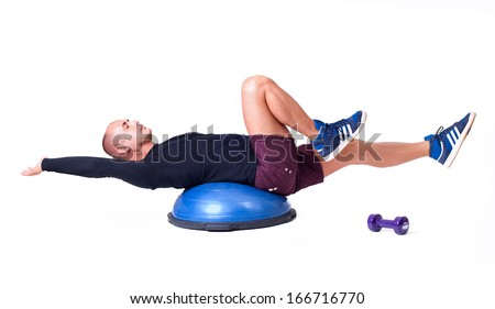 Sport man exercise with a pilates ball and dumbbells. Isolated on a white background. Studio shot