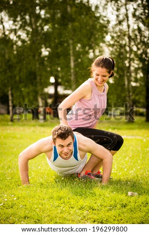 Sport man making push-ups while woman is sitting on him as a weight - stock photo