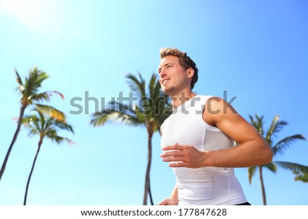 Sport man running. Male athlete runner jogging in compression t-shirt top training on palm trees beach. Fit handsome male fitness model jogging alone training for marathon run. Man in his twenties. - stock photo