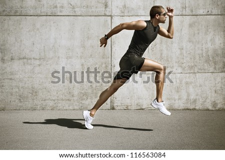 sport man starting running. Young man jogging front cement wall - stock photo