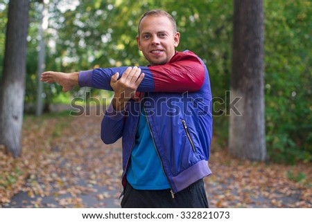 sport man stretching at the park autumn, doing exercises. Fitness concepts.