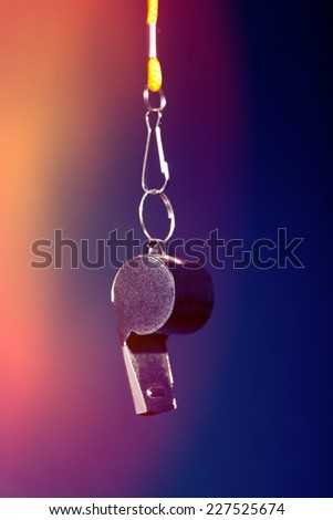 Sport metal whistle on color background - stock photo