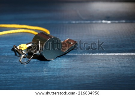 Sport metal whistle on color wooden background - stock photo