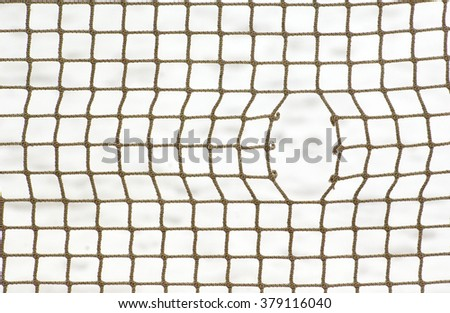 Sport net with hole on winter snow background - stock photo