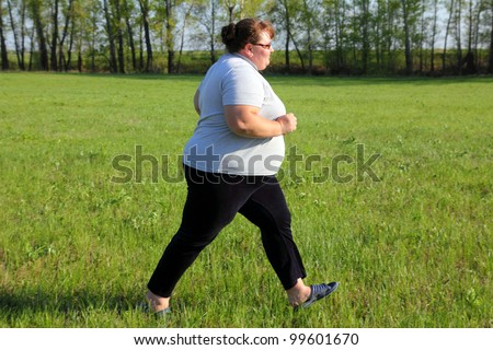 sport - overweight woman running on green meadow - stock photo