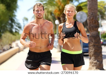 Sport people - active couple of runners running in city. Sexy fit young adults training cardio jogging under the summer sun sweating, man shirtless and woman in sports bra. Caucasian male and female. - stock photo