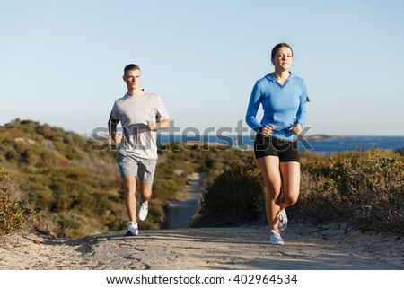 Sport runner jogging on beach working out with her partner - stock photo