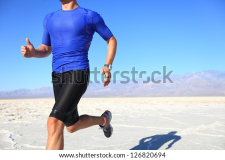 Sport - runner running and sprinting in desert. Athlete man during sprint run at great speed. Fitness man wearing compression clothes. - stock photo