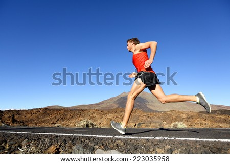 Sport running man - male runner training outdoors sprinting on mountain road in amazing landscape nature. Fit handsome jogger working out for marathon outside in summer. - stock photo