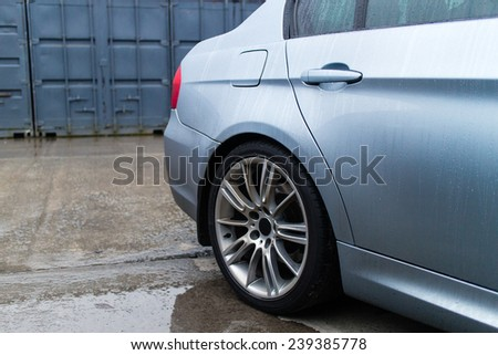 Sport sedan`s side. Containers in a background. - stock photo