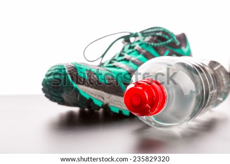 Sport shoe and a bottle of water closeup - stock photo