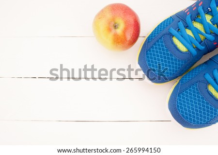Sport shoes and apple on white wooden background. Top view sport equipment. Selective focus - stock photo