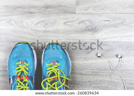 Sport shoes and headphones on a wood floor - stock photo