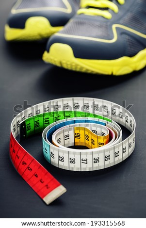 Sport shoes and  measuring tape on grey background - stock photo
