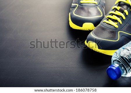 Sport shoes and water on grey background - stock photo