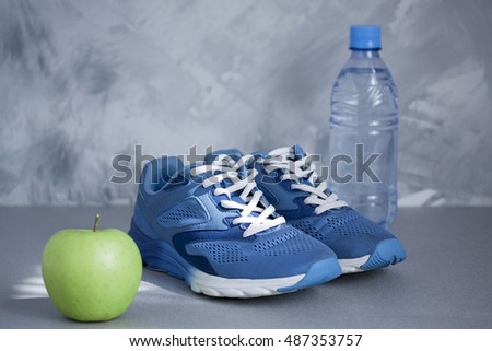 Sport shoes, apple, bottle of water on gray concrete background. Concept healthy lifestyle, sport and diet. Sport equipment. Focus is only on the sneakers.