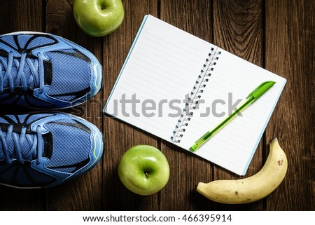Sport shoes, apples and bananas  on a  wooden background. Sport equipment, healthy and active lifestyles, copy space for text. Conceptual photo. Top view