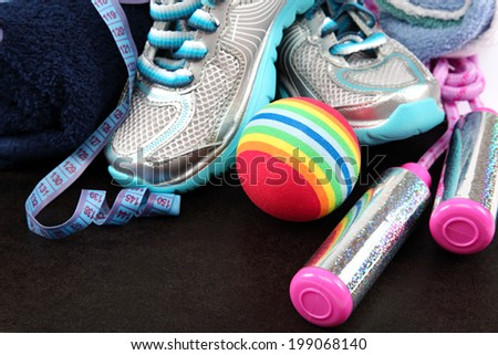 Sport shoes, equipment and measuring tape on a black background. - stock photo