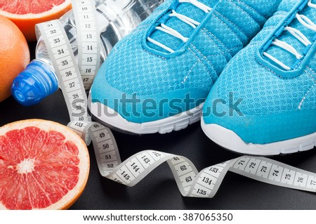 Sport shoes, grapefruit, bottle of water and measuring tape on dark background. Sport equipment. Concept healthy lifestyle, sport and diet. Selective focus - stock photo