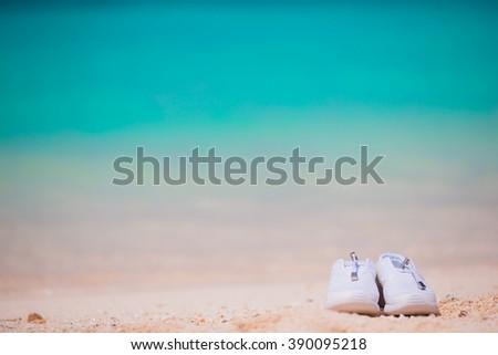 Sport shoes on white sandy beach - stock photo