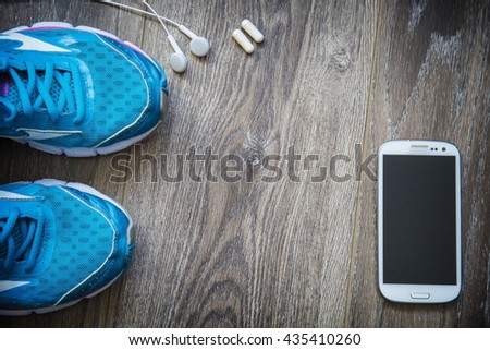 Sport shoes, phone and smart watch with set for sports activities on floor.