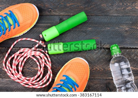 Sport shoes, skipping rope and bottle of water on the old wooden background. Sports equipment. Sport, diet and healthy life concept. Top view - stock photo