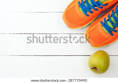 Sport shoes sneakers and apple on white wooden background. Top view sport equipment. Selective focus - stock photo