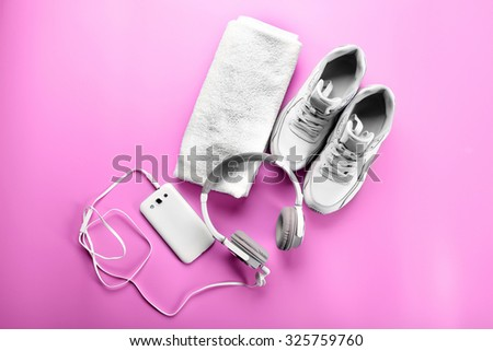 Sport shoes, towel and headphones on pink background - stock photo