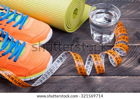 Sport shoes, yoga mat,  glass of water and centimeter on wooden background. Sport equipment. Concept healthy life. Selective focus - stock photo